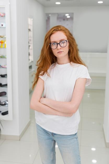 Retrato de mulher jovem e atraente com o braço cruzado em pé no showroom de óptica Foto gratuita