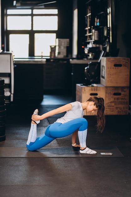 Retrato de mulher jovem e atraente fazendo exercícios de ioga ou pilates Foto gratuita