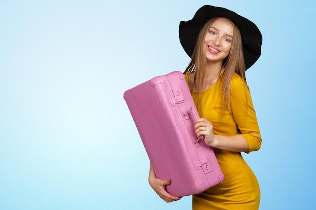 Retrato de mulher jovem e bonita com bolsa rosa Foto Premium