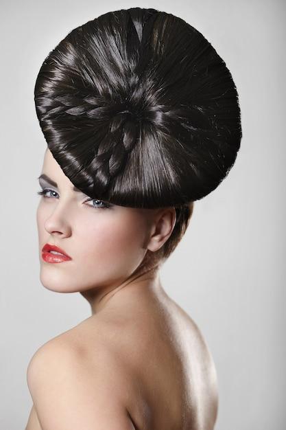 Retrato de mulher jovem e bonita com lábios vermelhos e estilo de cabelo incomum em cinza Foto gratuita