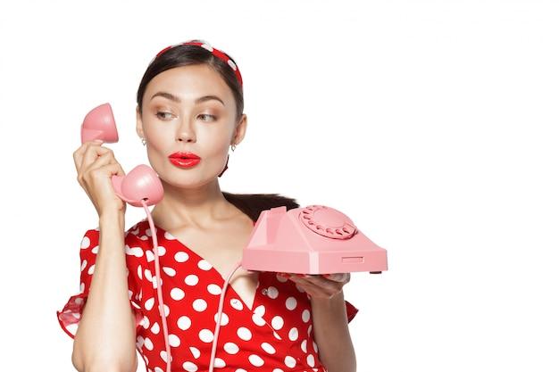 Retrato de mulher jovem e bonita com telefone, vestido em estilo pin-up. Foto Premium
