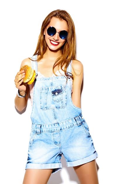 Retrato de mulher jovem e bonita elegante comendo hambúrguer Foto gratuita
