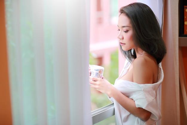 Retrato de mulher jovem e sexy acordar e ver a vista da janela do quarto Foto Premium