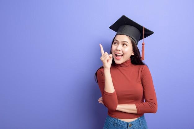 Retrato de mulher jovem estudante universitário com chapéu de formatura em violeta Foto Premium