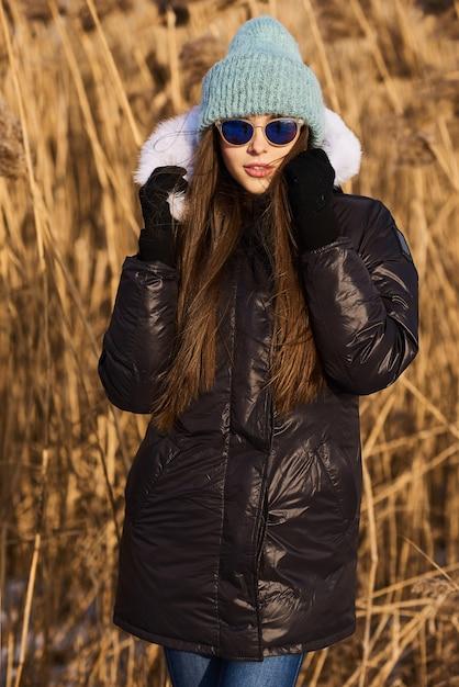 Retrato de mulher jovem feliz se divertindo em um lindo dia ensolarado de inverno Foto Premium