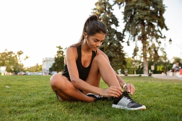 Retrato de mulher jovem fitness amarrar os cadarços Foto gratuita