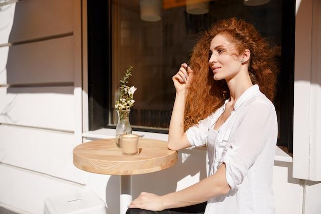 Retrato de mulher jovem ruiva bonita sentada em um café Foto gratuita