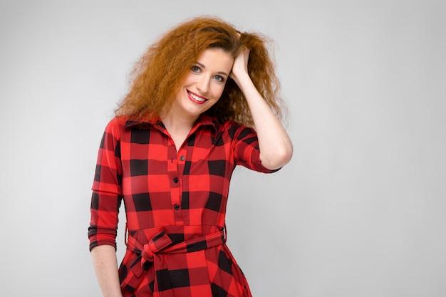 Retrato de mulher jovem ruiva feliz sorrindo, segurando a mão no cabelo na parede cinza Foto Premium