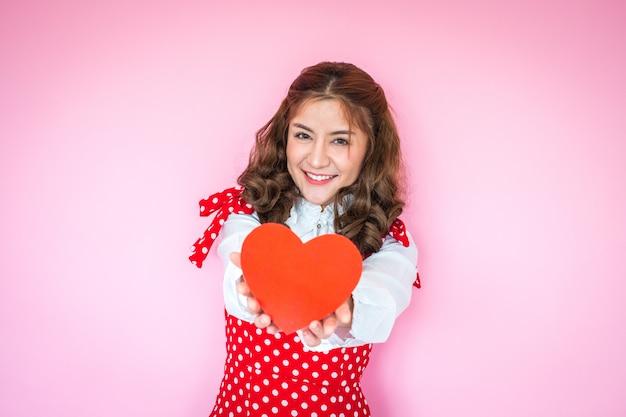 Retrato, de, mulher jovem, segurando, coração vermelho, frente, dela Foto Premium