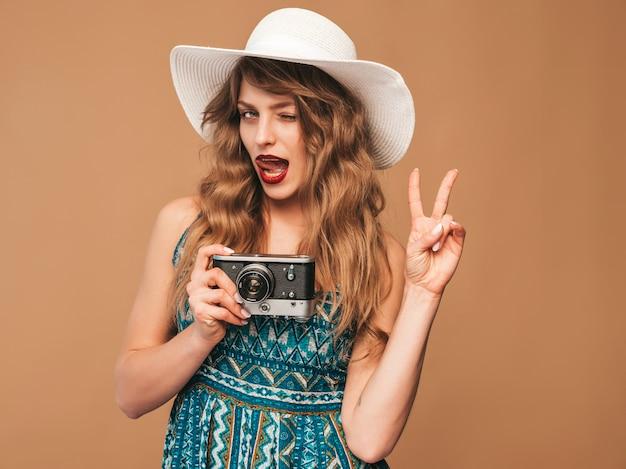 Retrato de mulher jovem sorridente alegre tirando foto com inspiração e com vestido de verão. menina segurando a câmera retro. modelo posando de chapéu Foto gratuita