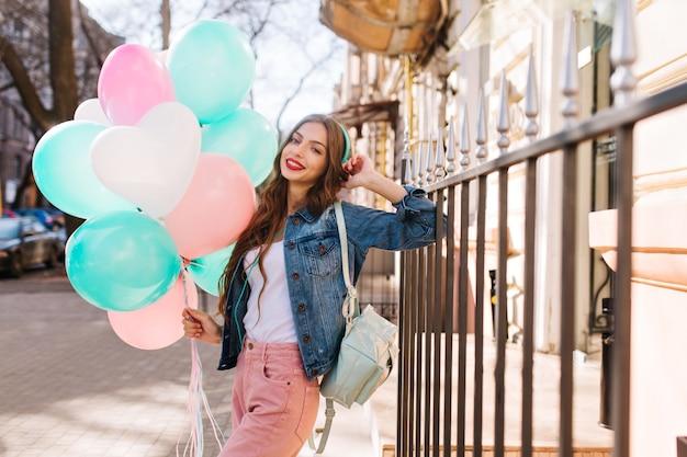 Retrato de mulher jovem sorridente, vestindo jaqueta jeans e calças elegantes, posando com balões de aniversário. Foto gratuita