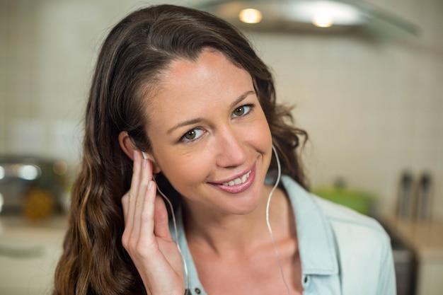 Retrato, de, mulher jovem, sorrindo, enquanto, escutar música, com, fones Foto Premium