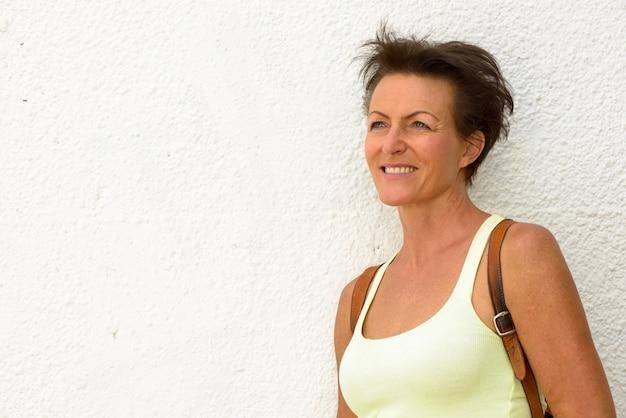 Retrato de mulher madura linda turista contra uma parede branca ao ar livre Foto Premium