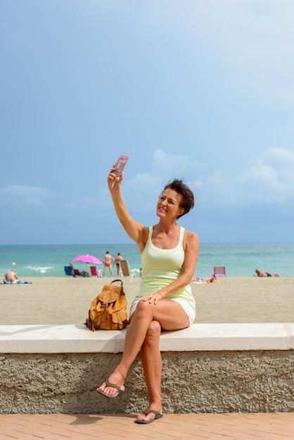 Retrato de mulher madura linda turista na praia ao ar livre Foto Premium