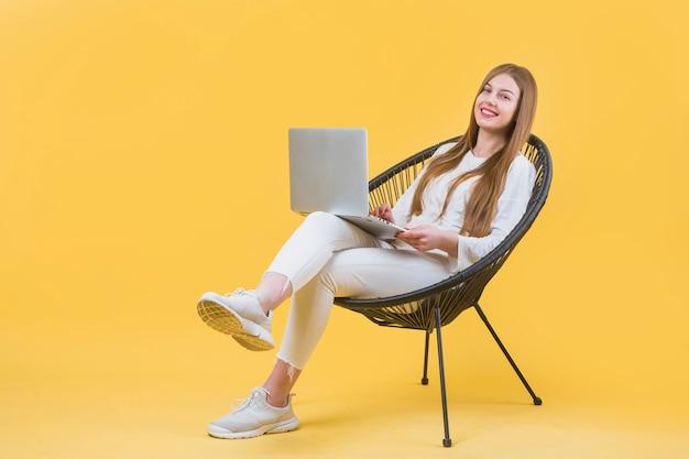 Retrato, de, mulher moderna, com, laptop, ligado, cadeira Foto gratuita