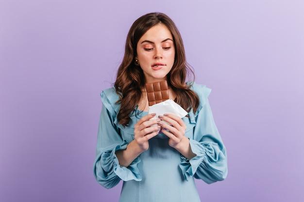 Retrato de mulher morena engraçada mordendo o lábio em antecipação ao saboroso almoço. menina de vestido azul parece um delicioso chocolate. Foto gratuita
