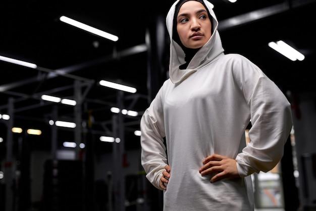 Retrato de mulher muçulmana esportiva séria posando para a câmera olhando para o lado no ginásio. em hijab branco. conceito de esporte Foto Premium