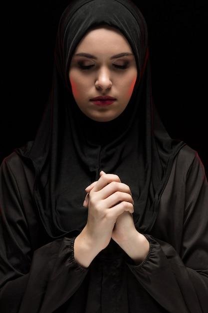 Retrato de mulher muçulmana séria jovem bonita vestindo preto hijab com os olhos fechados como rezar conceito sobre fundo preto Foto Premium
