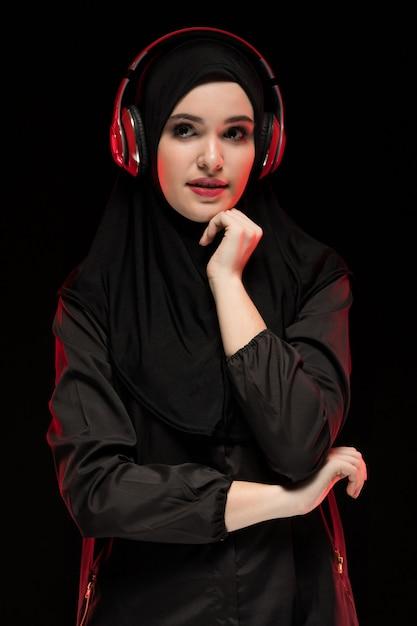 Retrato de mulher muçulmana usando hijab preto, ouvindo música em fones de ouvido Foto Premium