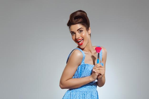 Retrato de mulher pin-up bonita no estúdio segurando o pincel de maquiagem Foto gratuita