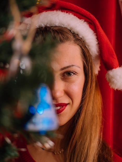 Retrato de mulher por trás da árvore de natal. menina de chapéu de papai noel Foto Premium