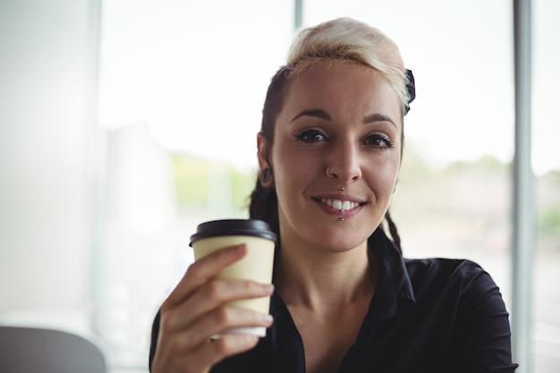 Retrato, de, mulher segura, descartável, xícara café Foto gratuita