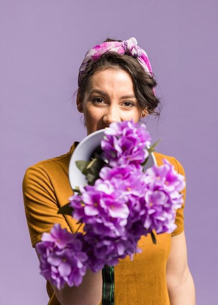 Retrato de mulher segurando na frente de seu megafone e flores Foto gratuita