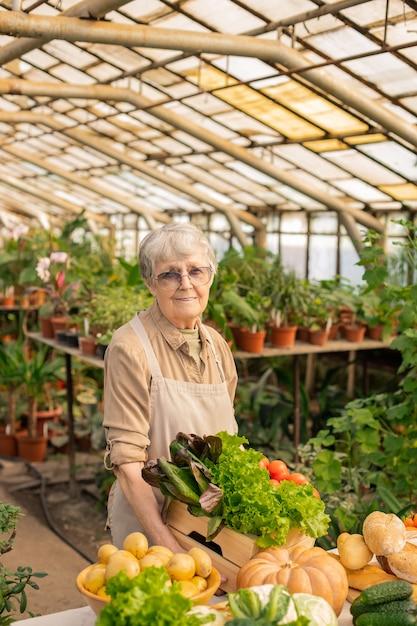 Retrato de mulher sênior com avental em pé no balcão e preparando produtos orgânicos para venda Foto Premium