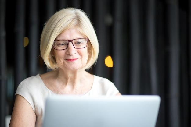 Retrato de mulher sênior positiva usando laptop Foto gratuita