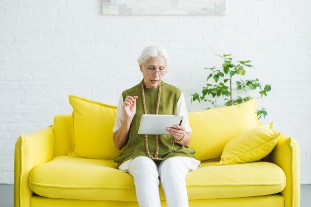 Retrato, de, mulher sênior, sentando, ligado, sofá amarelo, olhar, tablete digital Foto gratuita