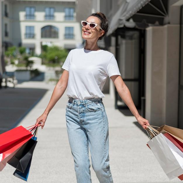 Retrato de mulher sorridente andando com sacolas de compras Foto gratuita