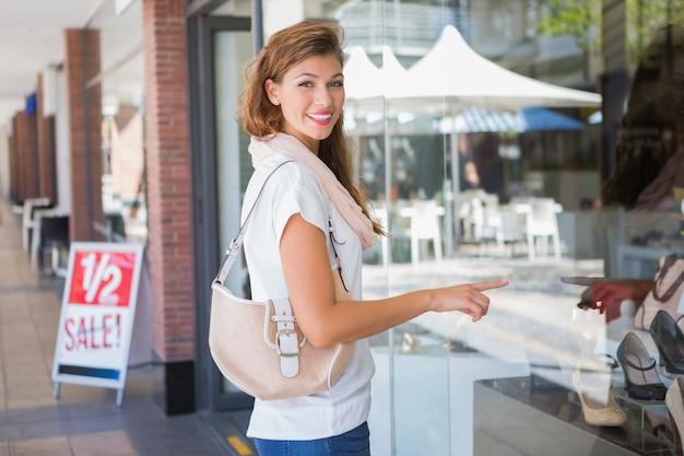Retrato de mulher sorridente apontando a janela e olhando a câmera Foto Premium