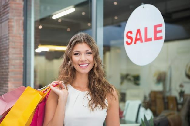 Retrato de mulher sorridente com sacolas de compras olhando câmera Foto Premium