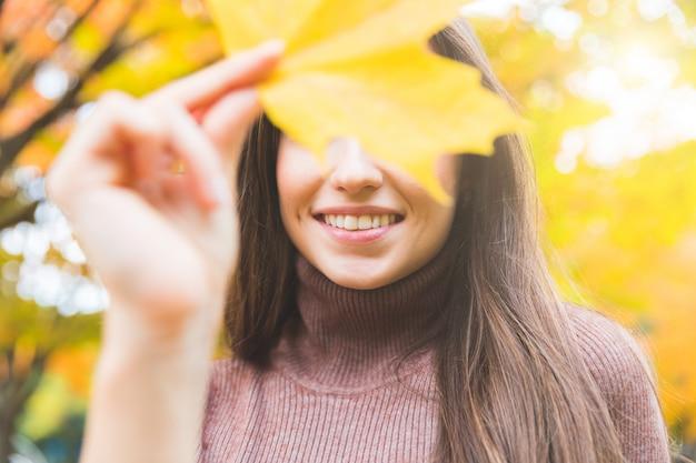 Retrato de mulher sorridente com uma folha amarela no outono Foto Premium