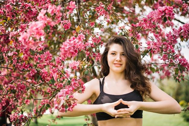 Retrato, de, mulher sorridente, fazendo, ioga, mudra, gesto, parque Foto gratuita