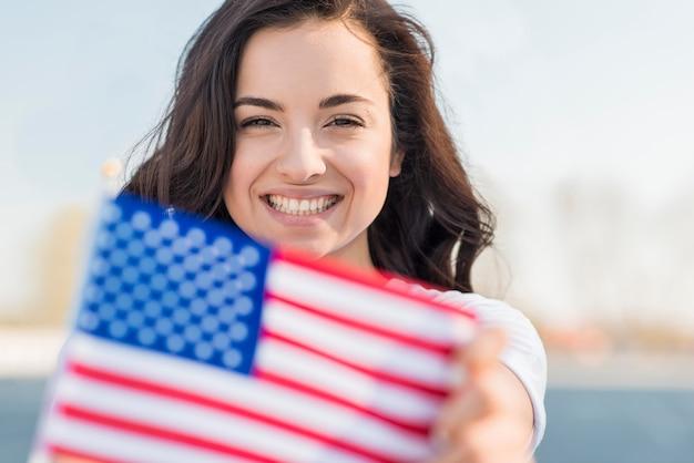 Retrato, de, mulher sorridente, segurando, eua bandeira Foto gratuita