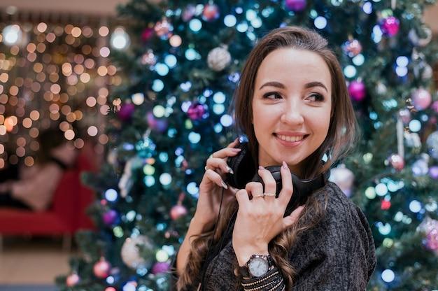 Retrato de mulher sorridente usando fones de ouvido perto da árvore de natal, olhando para longe Foto gratuita
