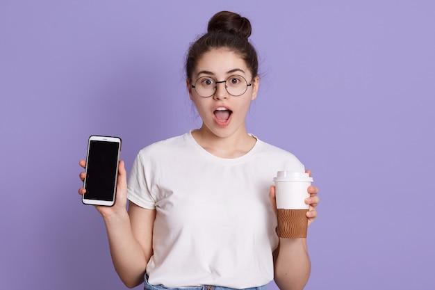 Retrato de mulher surpreendida chocada com cabelos escuros, segurando tirar a xícara de café e telefone celular Foto gratuita