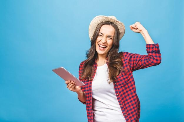 Retrato de mulher vencedora animada segurando o tablet pc Foto Premium
