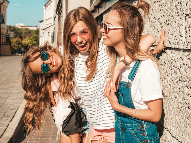 Retrato de mulheres despreocupadas sexy, posando na rua perto da parede. modelos positivos se divertindo em óculos de sol. Foto gratuita