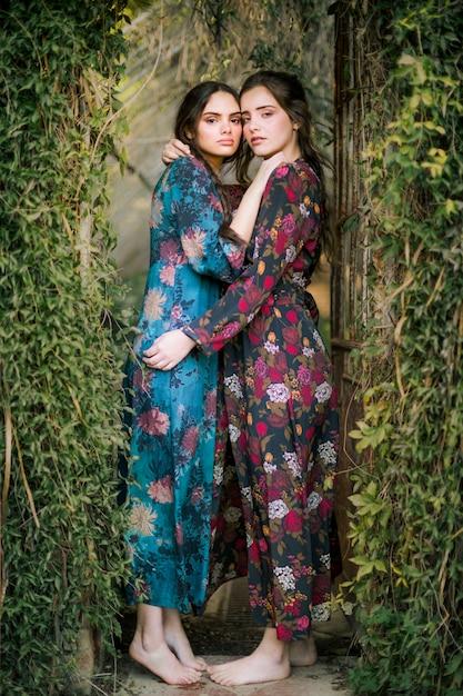 Retrato, de, mulheres, ficar, e, abraçando, um ao outro Foto gratuita