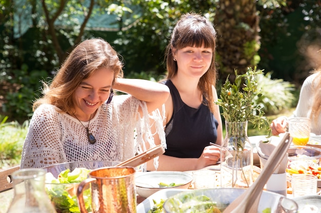 Retrato, de, mulheres sorridentes, sentando, junto, em, partido jardim Foto gratuita