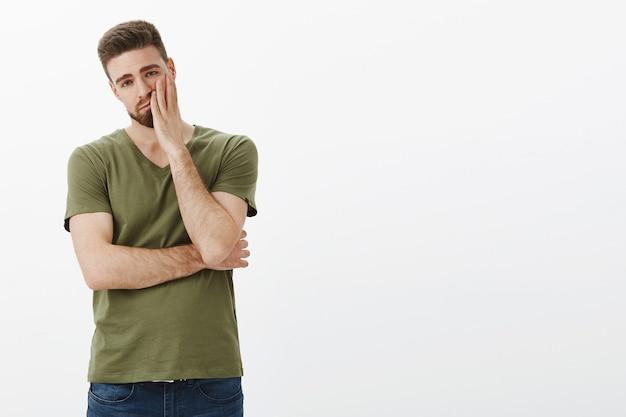 Retrato de namorado bonito cansado e indiferente sofrendo lavagem cerebral durante uma discussão cara a cara parecendo exausto e entediado com rosto esgotado e angustiado sobre a parede branca Foto gratuita