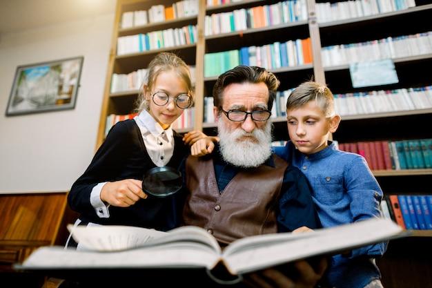 Retrato de netos adolescentes atraentes e experiente avô barbudo sênior que passar algum tempo juntos na biblioteca na leitura de livro interessante. estante no fundo Foto Premium