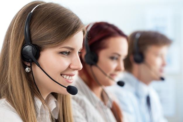 Retrato de operária de call center acompanhada por sua equipe. operador de suporte ao cliente sorridente no trabalho. conceito de ajuda e suporte Foto Premium