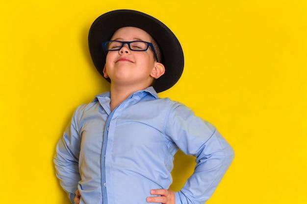 Retrato de orgulhoso lindo garotinho no chapéu e camisa isolado no amarelo Foto Premium