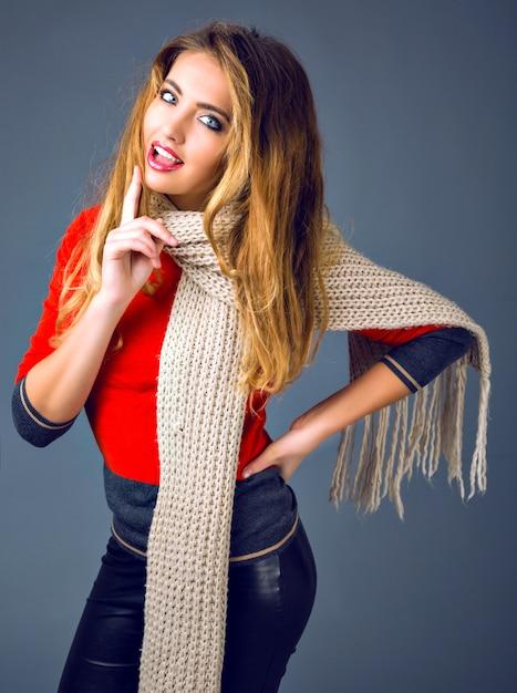 Retrato de outono inverno retrato de moda estúdio positivo, alegre mulher loira brincando com seu lenço, roupa casual inteligente. Foto gratuita