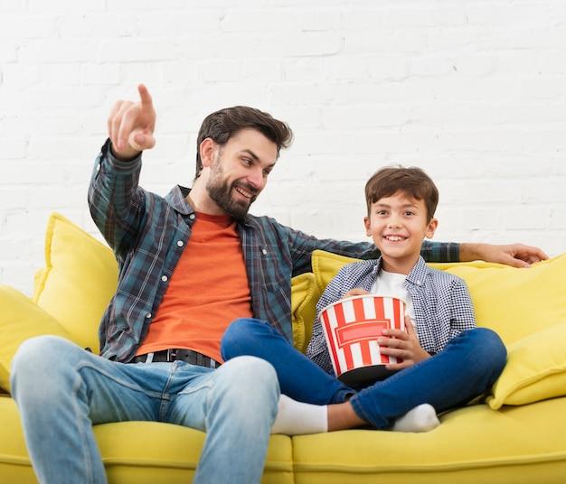Retrato de pai e filho sentado no sofá Foto gratuita