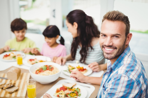 Retrato de pai sorridente com a família na mesa de jantar Foto Premium