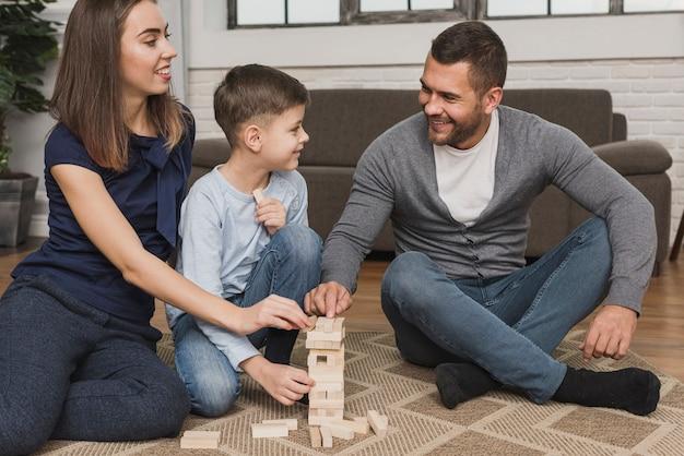 Retrato de pais adoráveis brincando com filho Foto gratuita